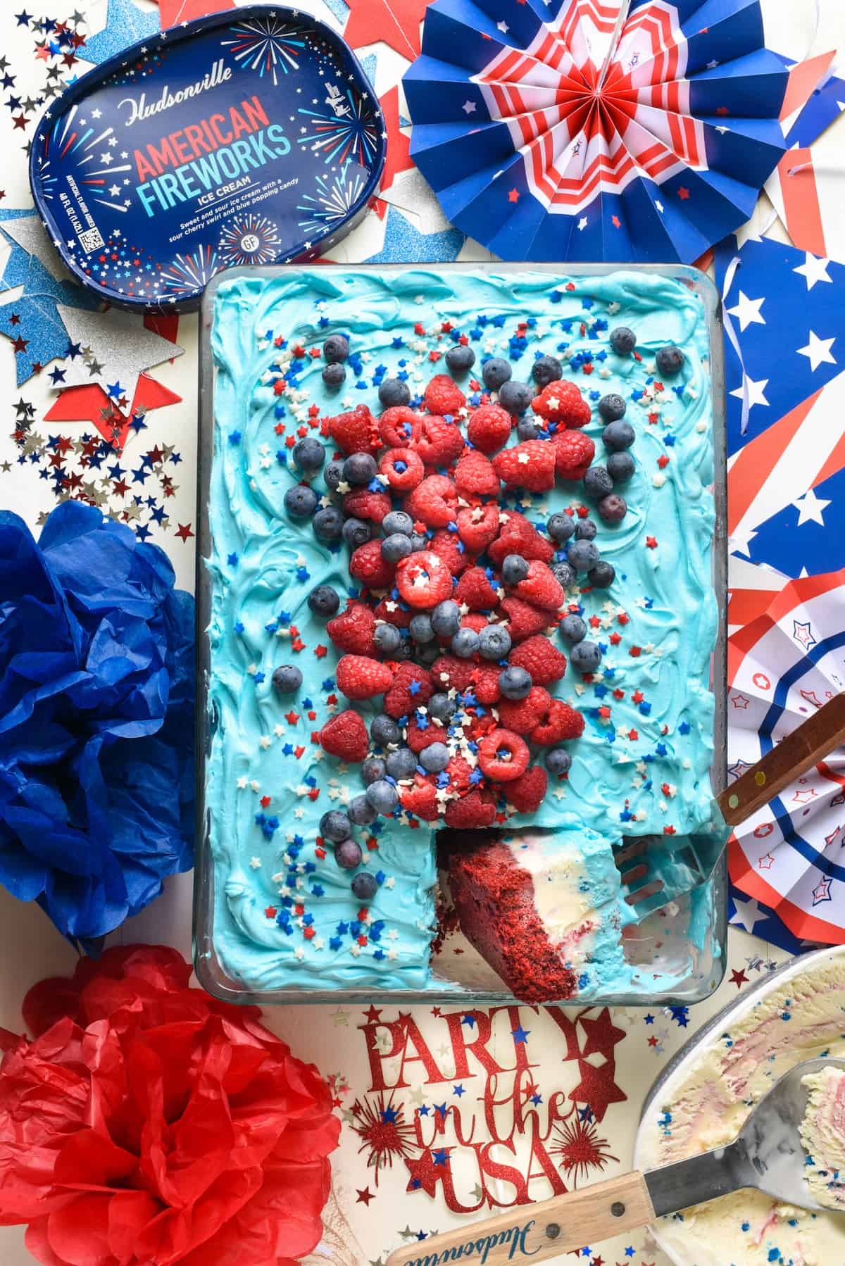 Overhead shot of red white and blue ice cream cake with one piece cut and turned. Cake is topped with berries and sprinkles.