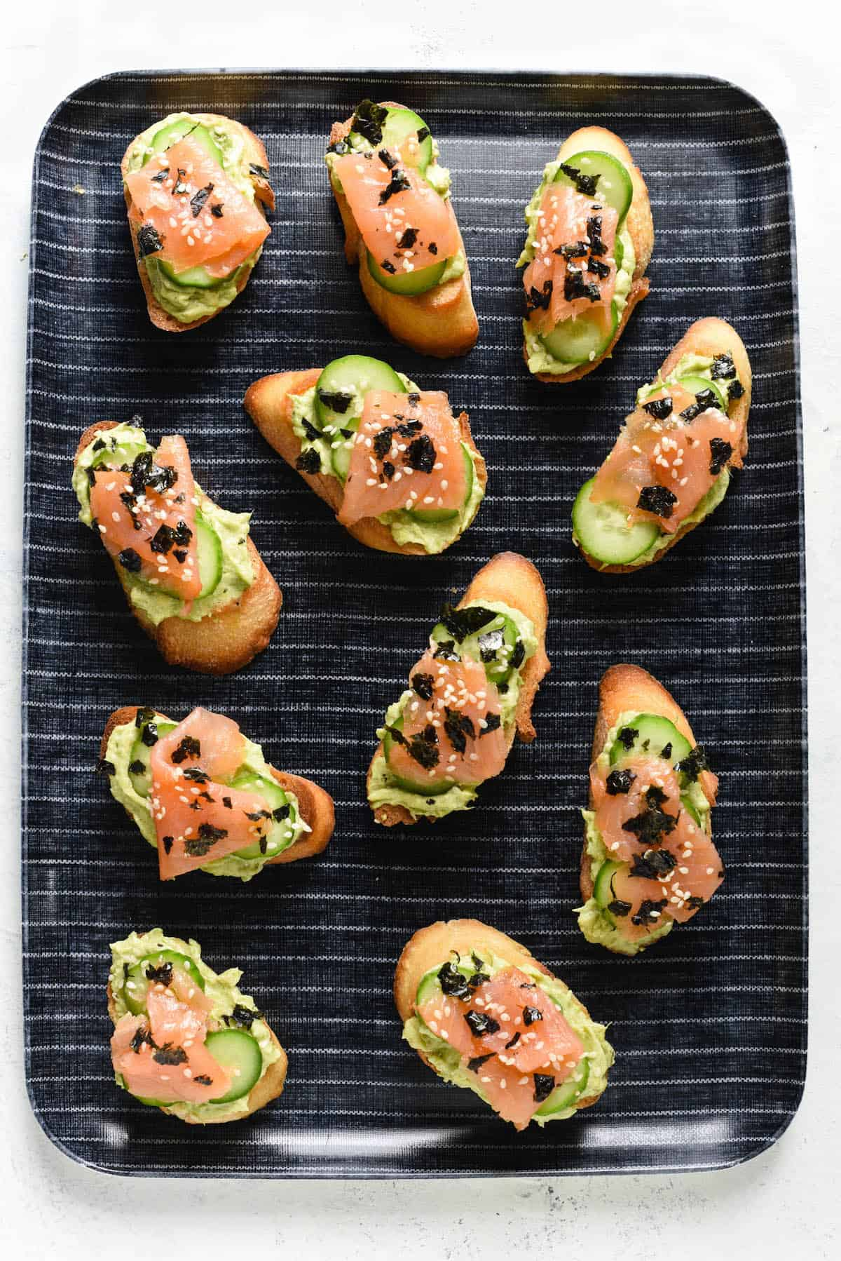 Avocado, salmon and cucumber crostini arranged on blue and white striped tray.