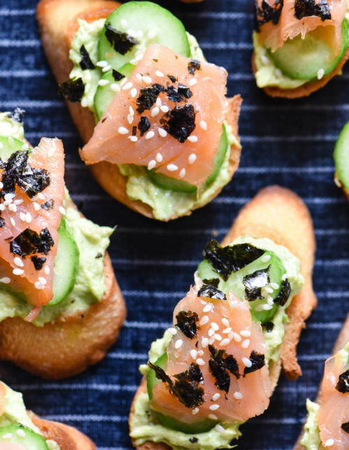 Toasted baguette topped with avocado spread, cucumber and smoked salmon, on top of blue and white striped serving tray.