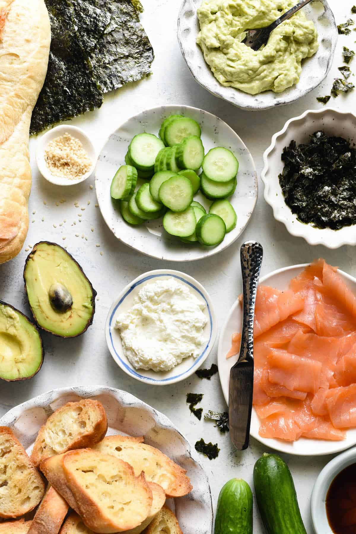 Ingredients for salmon bruschetta arranged in small bowls on white tabletop. Avocado spread, sliced cucumber, seaweed, smoked salmon, cream cheese, sesame seeds, sliced baguette.