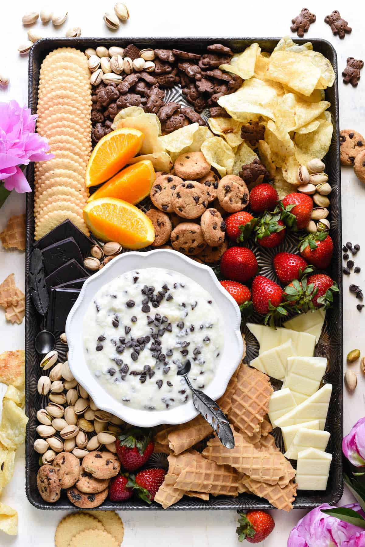 Overhead shot of large pan with bowl of cannoli dip and cookies, fruit, nuts and potato chips for dipping.