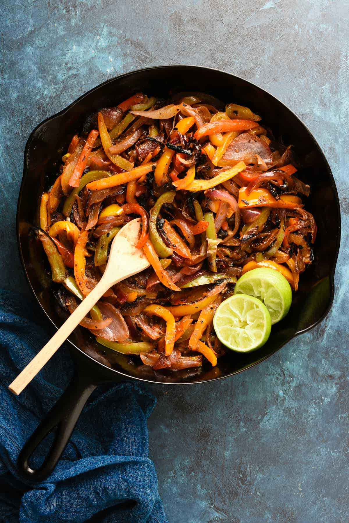 Cast iron skillet filled with cooked fajita veggies, with wooden spoon and lime halves.