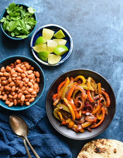 Bowls of sauteed peppers and onions, pinto beans, lime wedges and cilantro on blue background with charred tortillas.