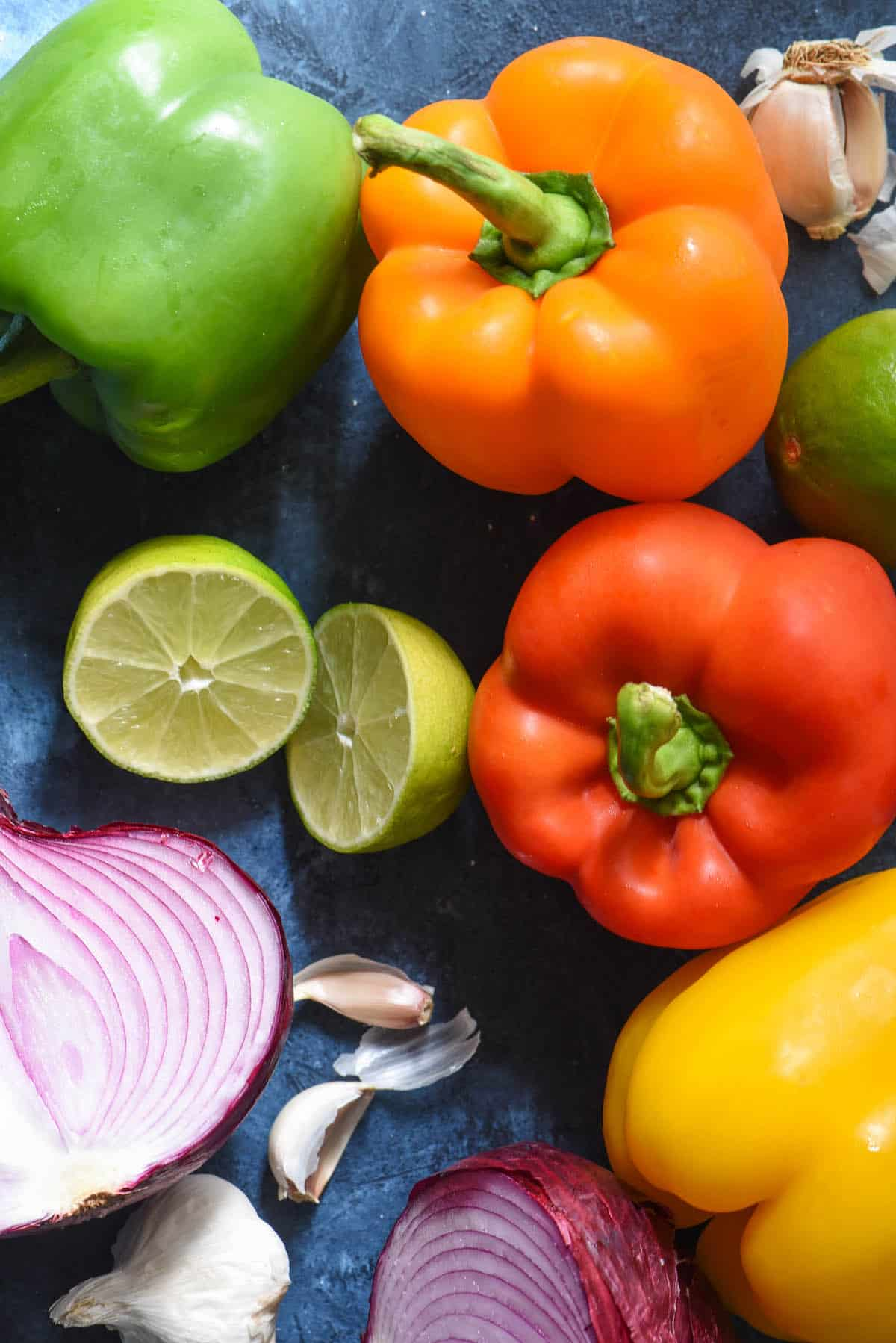 Bell peppers, lime, garlic and red onion on blue background.