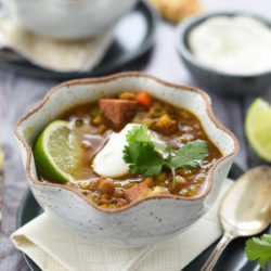 Two fluted rustic bowls of Instant Pot lentil soup topped with yogurt, cilantro and limes wedges.