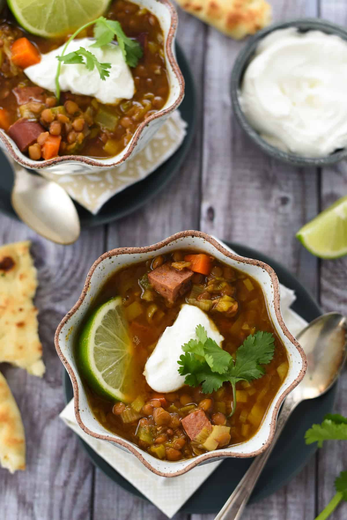 Overhead photos of two bowls of soup with lentils and sausage, with bowl of yogurt and naan bread alongside.