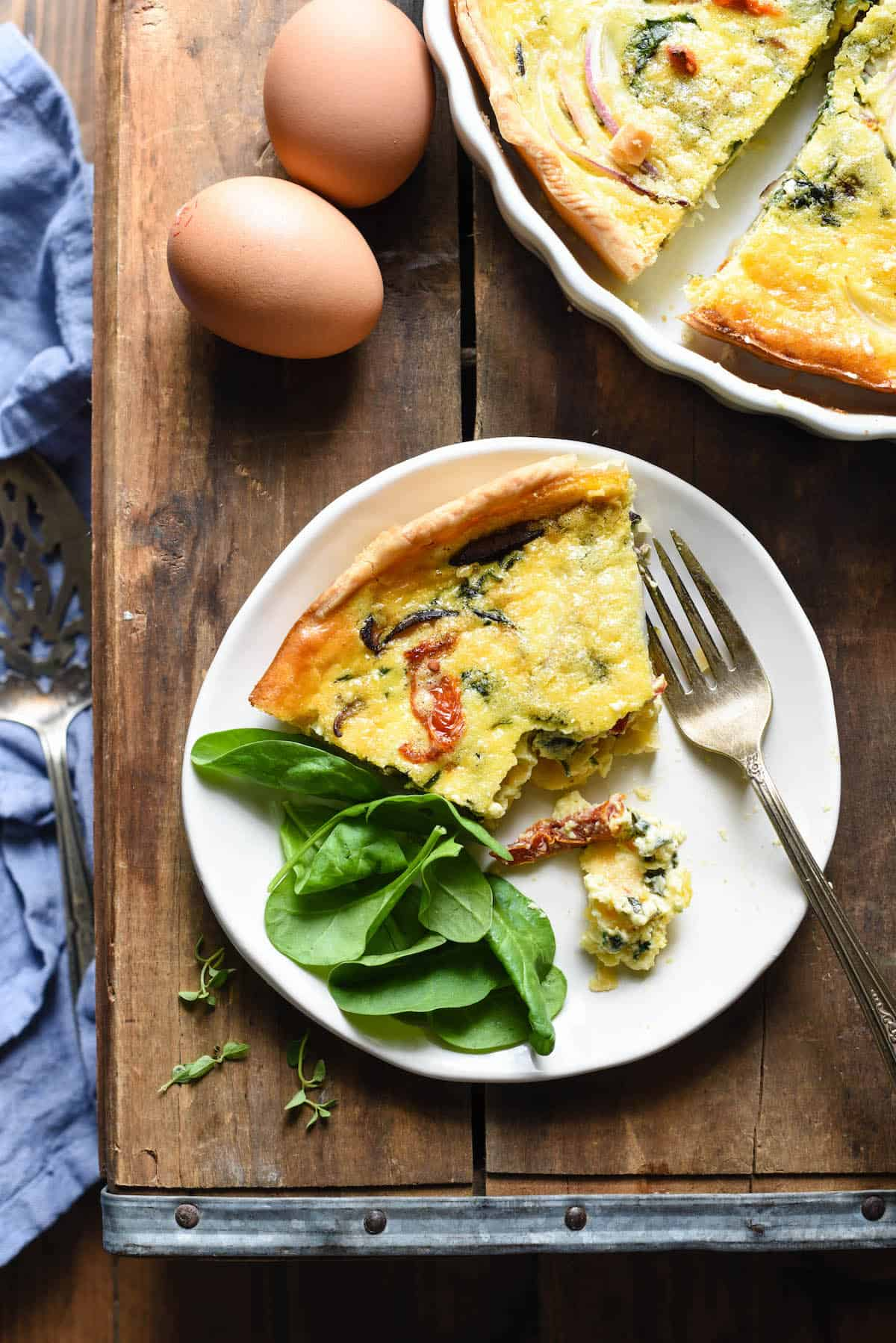 Overhead image of small white place with slice of egg pie and spinach on the side.