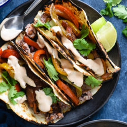 Overhead photo of three vegetarian fajitas on black plate with lime wedges.