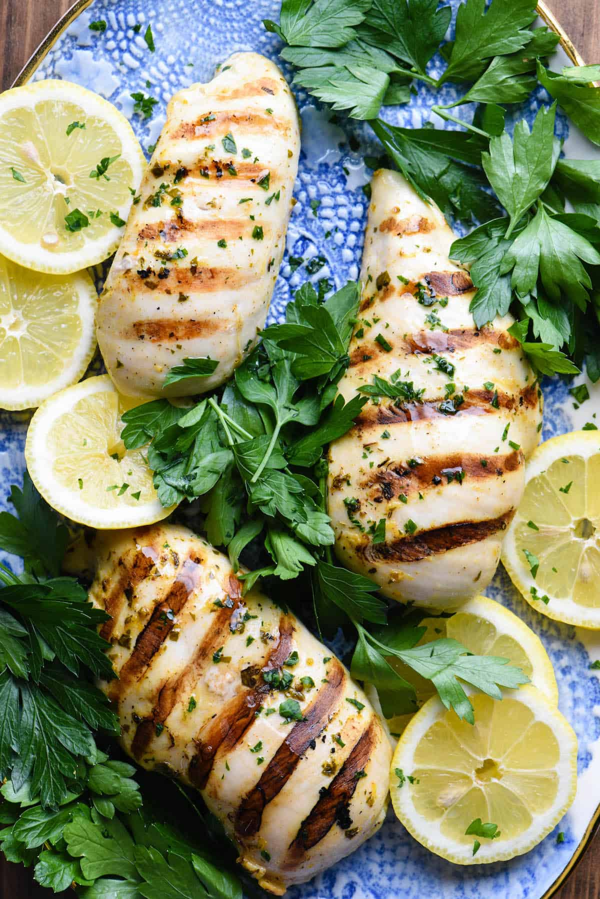 Cooked chicken pieces on pretty blue platter with herbs and lemons slices.