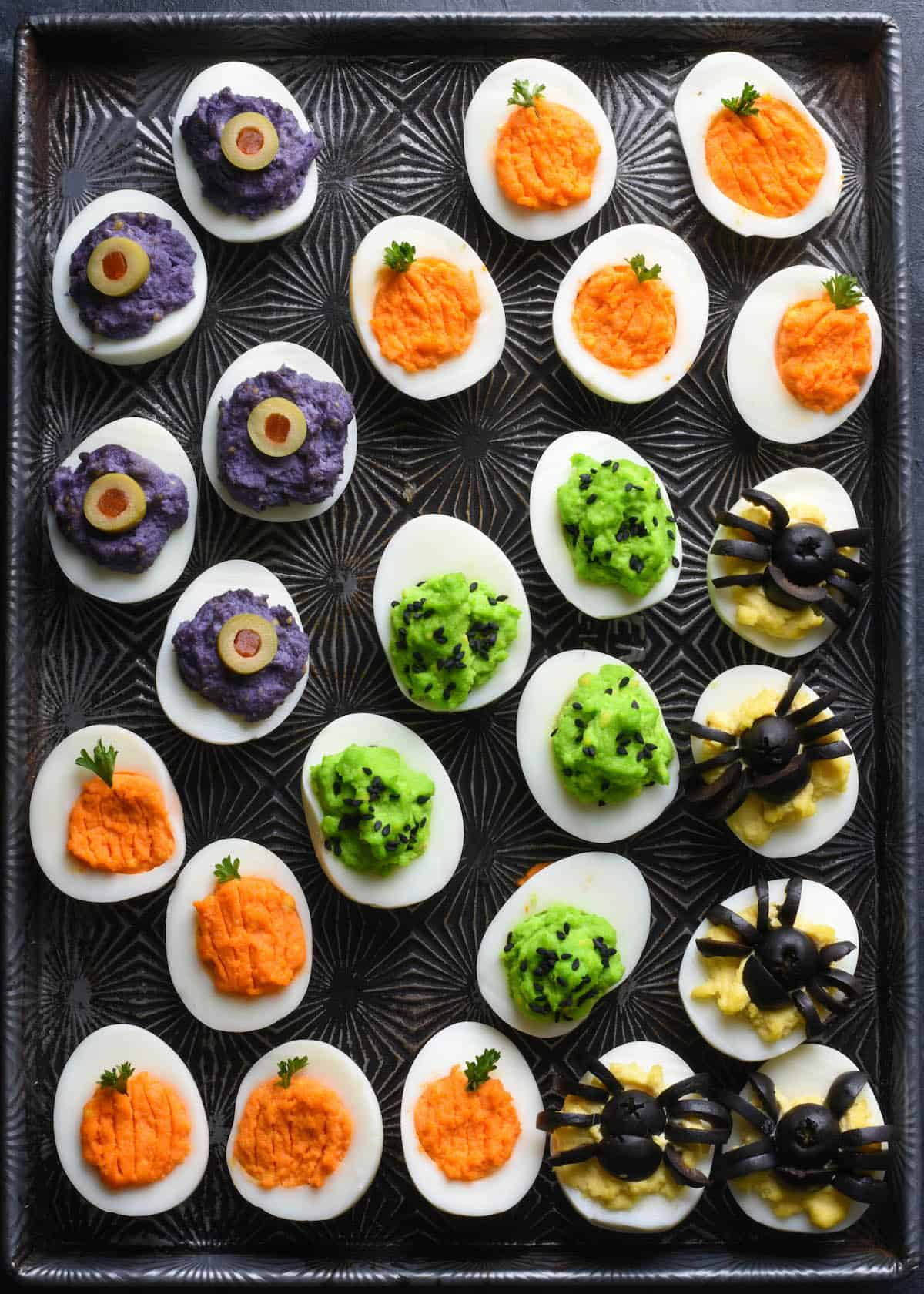 Cookie sheet with various types of Halloween decorated deviled eggs arranged on top.