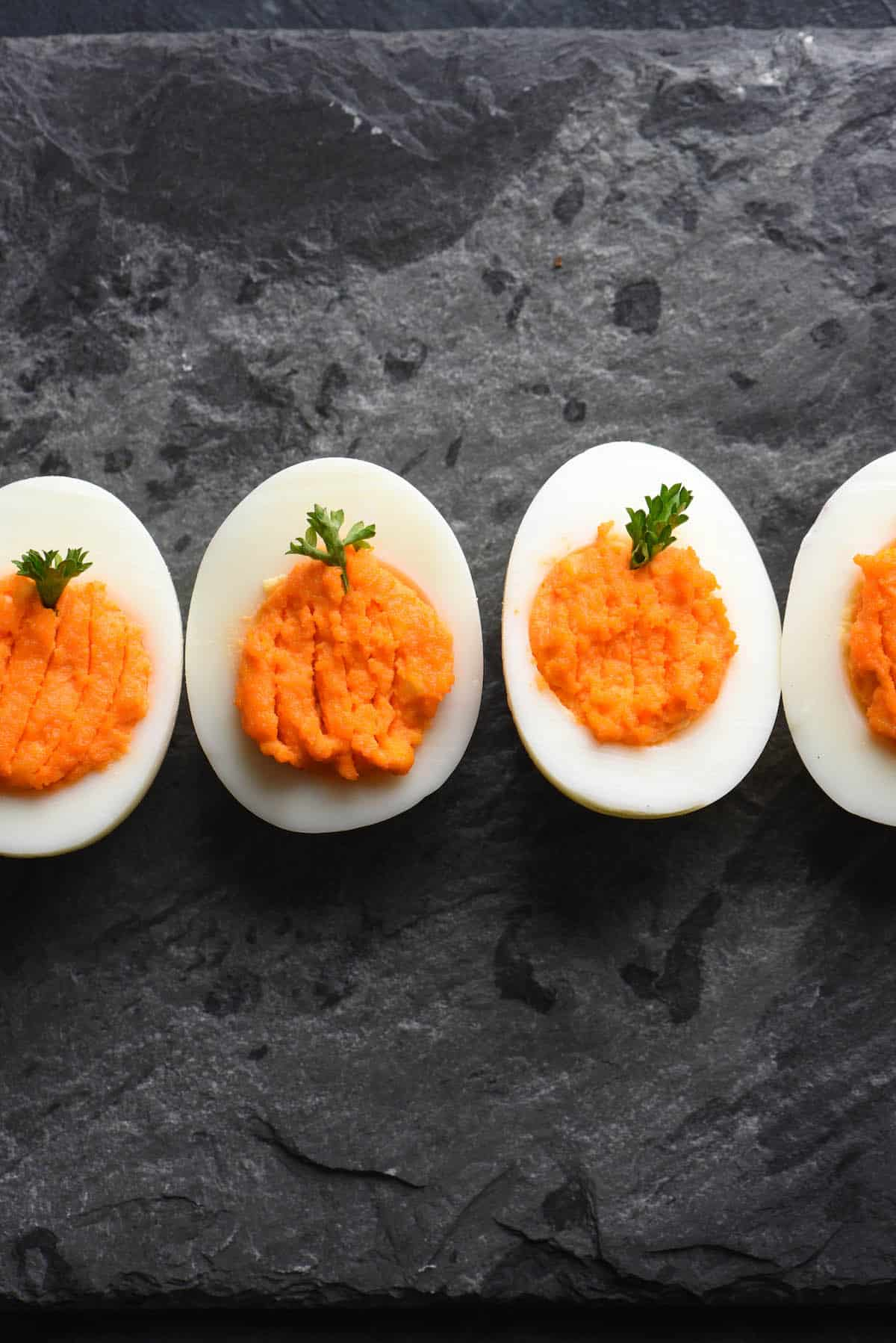 "Devilled eggs with orange yolks, decorated with parsley ""stems"" to look like pumpkins."