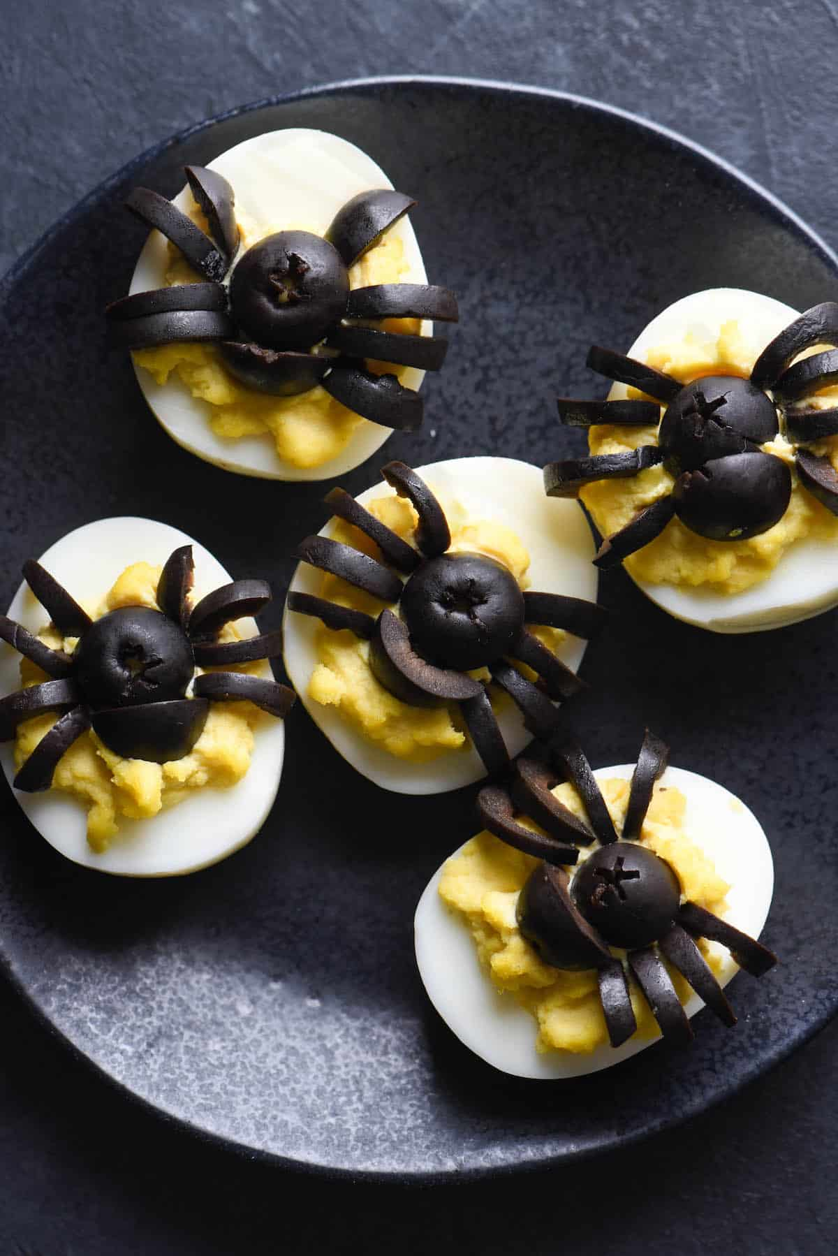 Black plate with deviled eggs on top. Black olives cut into the shape of spiders decorate the tops of the eggs.