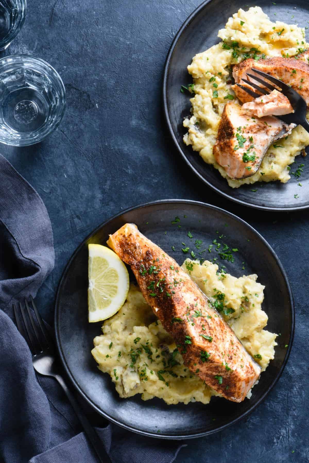 Dark background topped with two black plates. Plates are filled with instant pot salmon and mashed potatoes. Water glasses and napkin nearby.