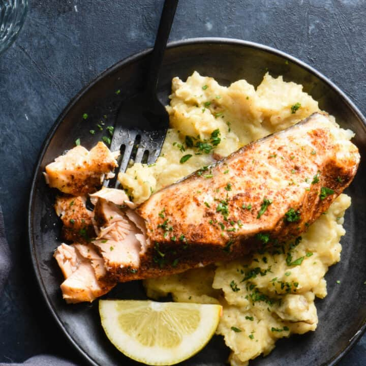 Black plate on dark background topped with mashed potatoes, salmon fillet and lemon wedge.