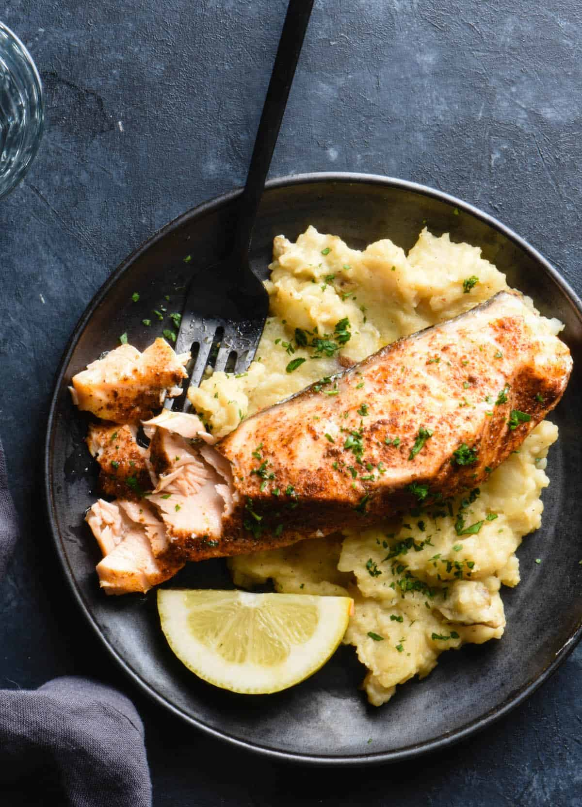 Black plate on dark background filled with mashed potatoes and salmon. Black fork is cutting into salmon fillet.