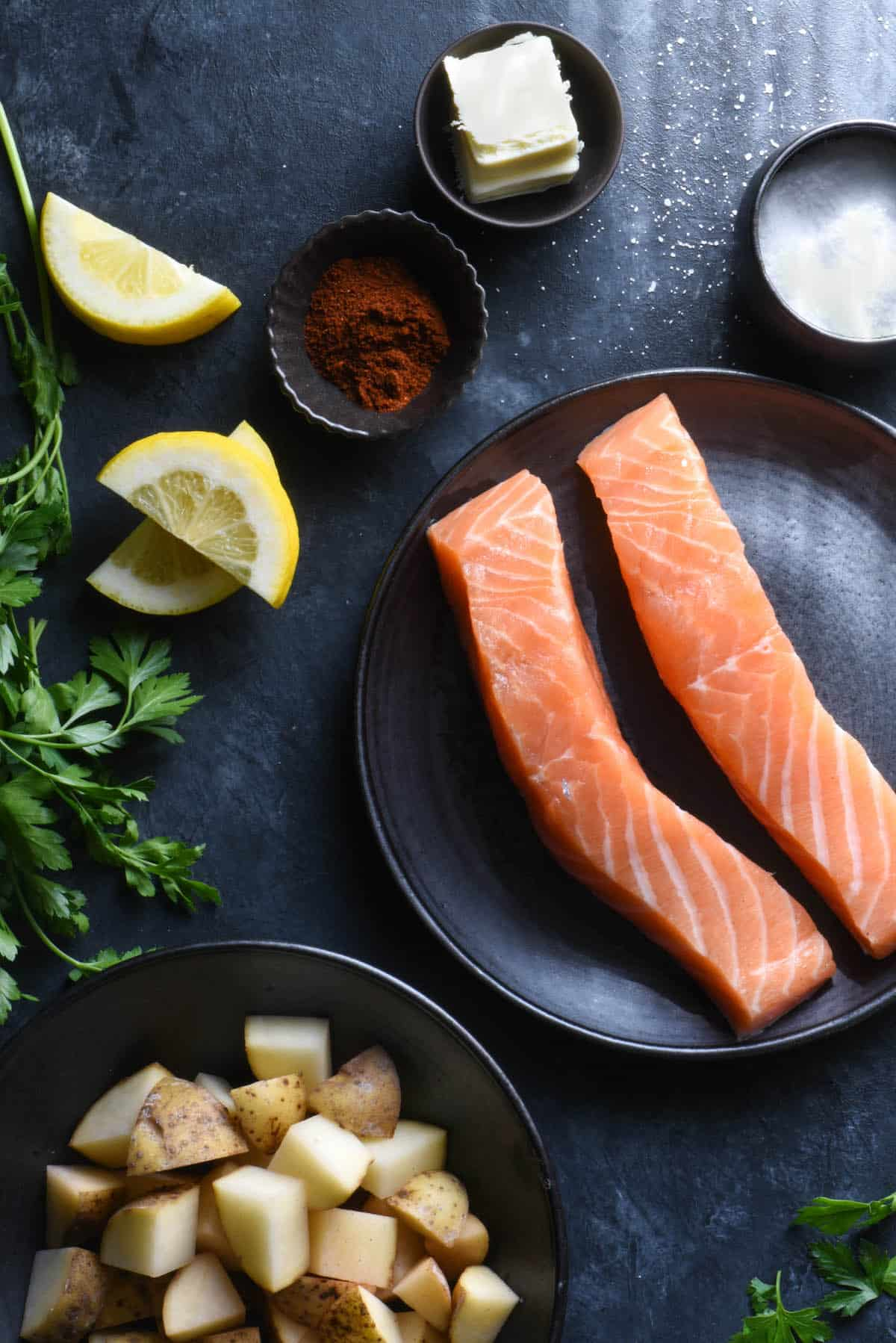 Dark background topped with ingredients: salmon fillets, raw chopped potatoes, parsley, lemon wedges, spices and butter.