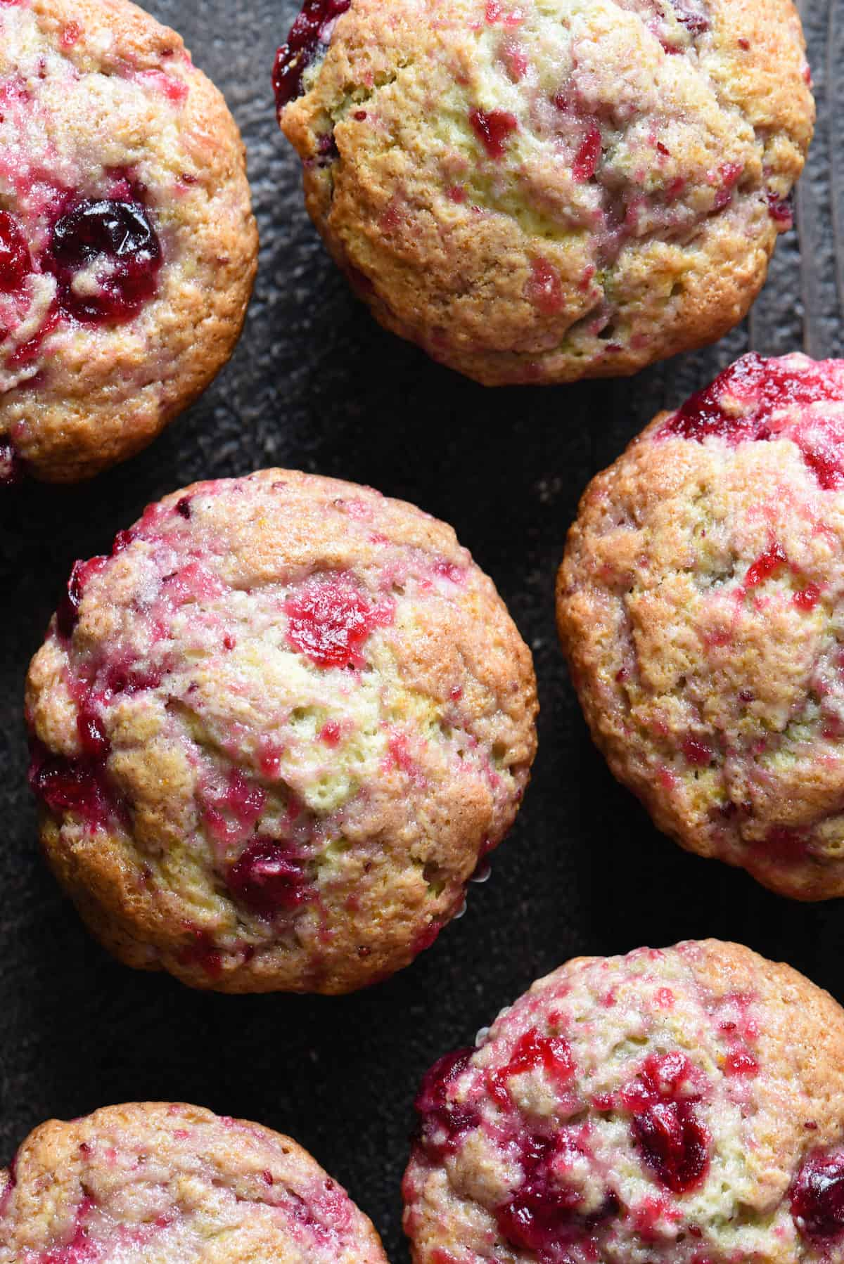 Overhead photo of six cranberry sauce muffins.
