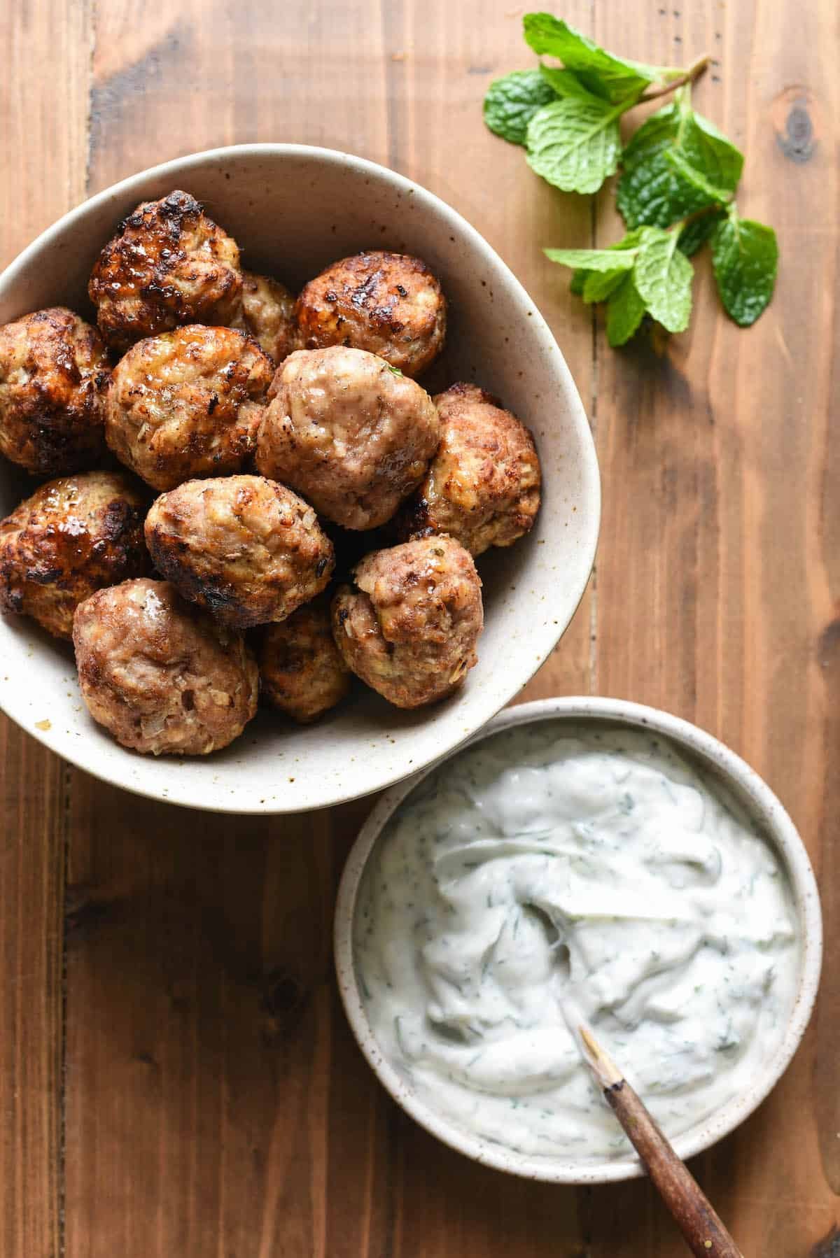 A bowl of air fryer turkey meatballs and a bowl of herbed yogurt sauce, with a mint sprig.