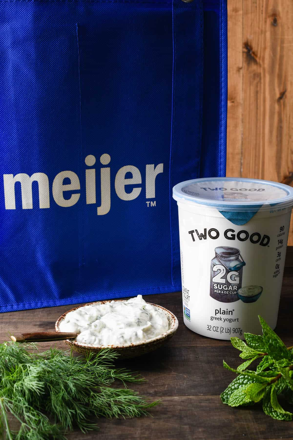 Container of Two Good Greek yogurt, bowl of yogurt sauce, mint and dill, with blue reusable Meijer bag in background.