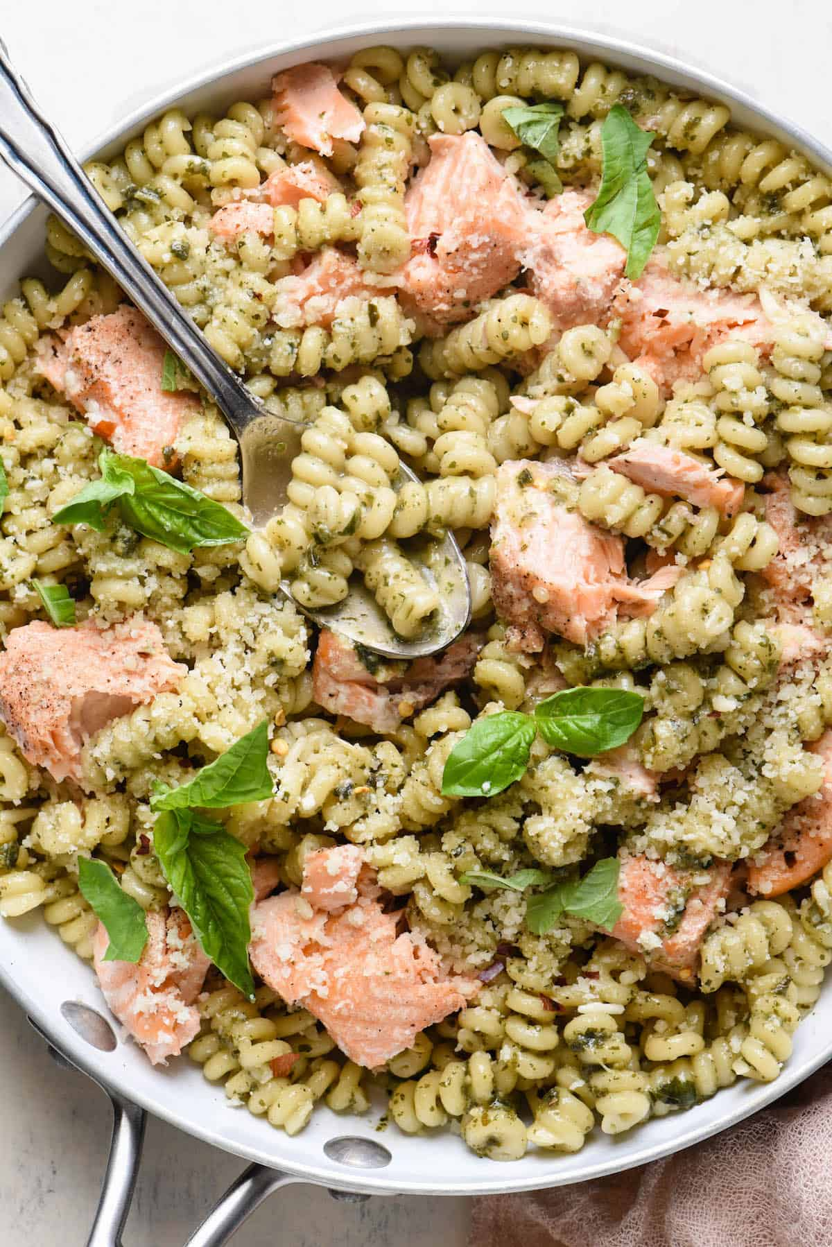 Closeup photo of noodles with pesto and salmon, in white skillet.