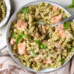Overhead photo of skillet filled with spiral shaped noodles tossed with pesto, and chunks of salmon.