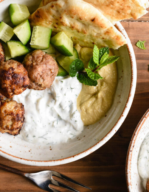Overhead photo of rustic bowl filled with turkey meatballs, chopped cucumber, hummus, yogurt sauce, naan and a mint sprig garnish.