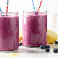Two glass jars filled with bright purple liquid and printed paper straws.