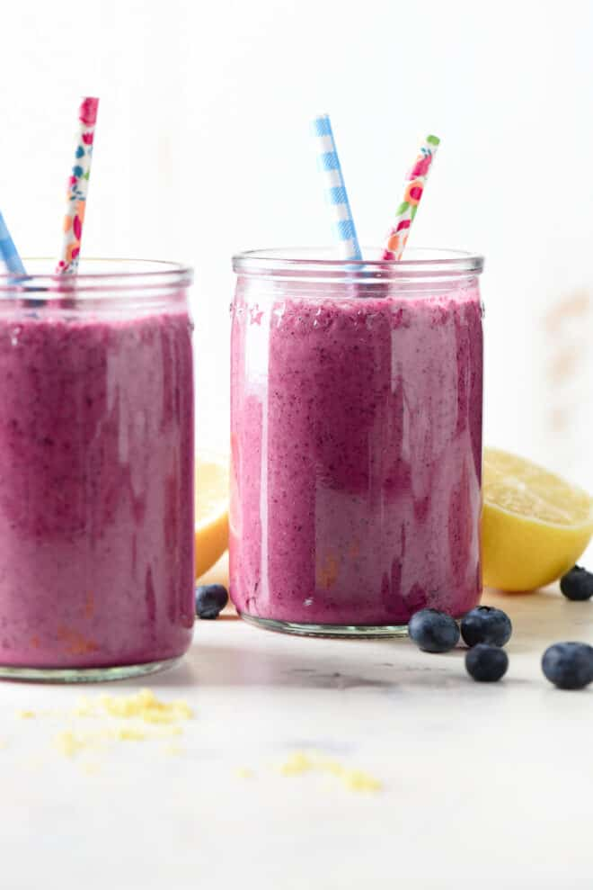 Two glass jars filled with bright purple blended fruit drink and fun straws.