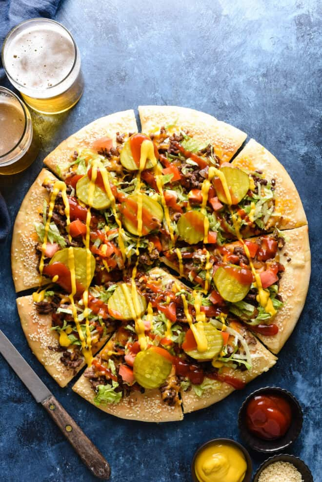 Overhead photo of pizza topped with burger toppings, with two beers nearby.