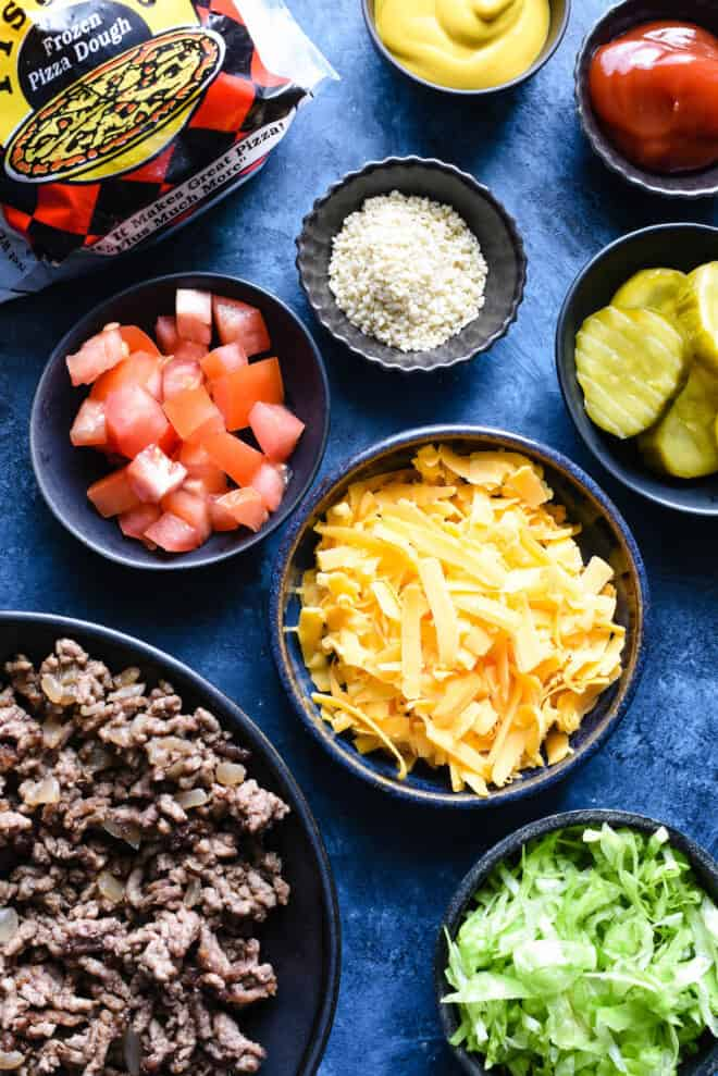 Blue tabletop with small bowls of pizza toppings like ground beef, shredded yellow cheese, diced tomatoes, pickles, sesame seeds, shredded lettuce, ketchup and mustard.