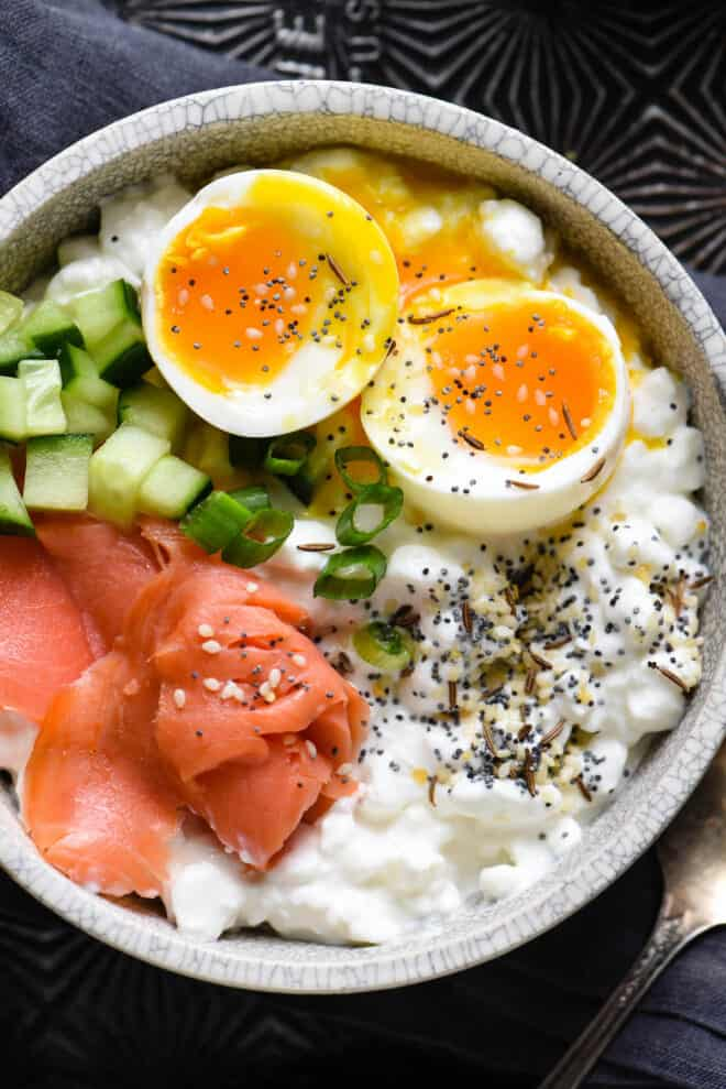 Closeup on savory cottage cheese breakfast bowl topped with soft egg, lox, cucumber and green onion.