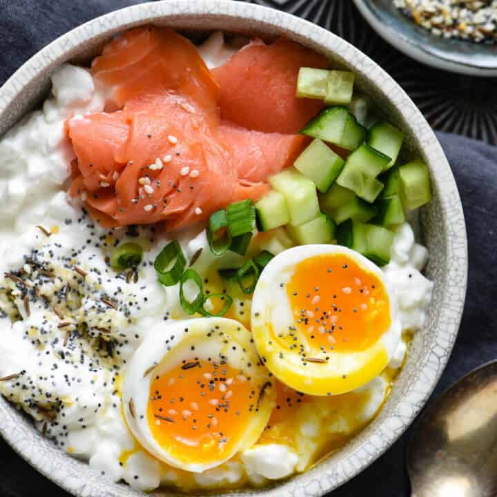 Gray bowl filled with cottage cheese, soft egg, smoked salmon and green onions.