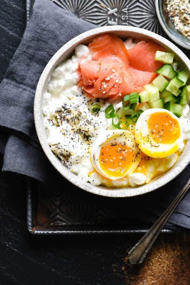 Gray bowl on top of dark gray napkin. Bowl is filled with a savory cottage cheese breakfast, including a soft egg and smoked salmon.