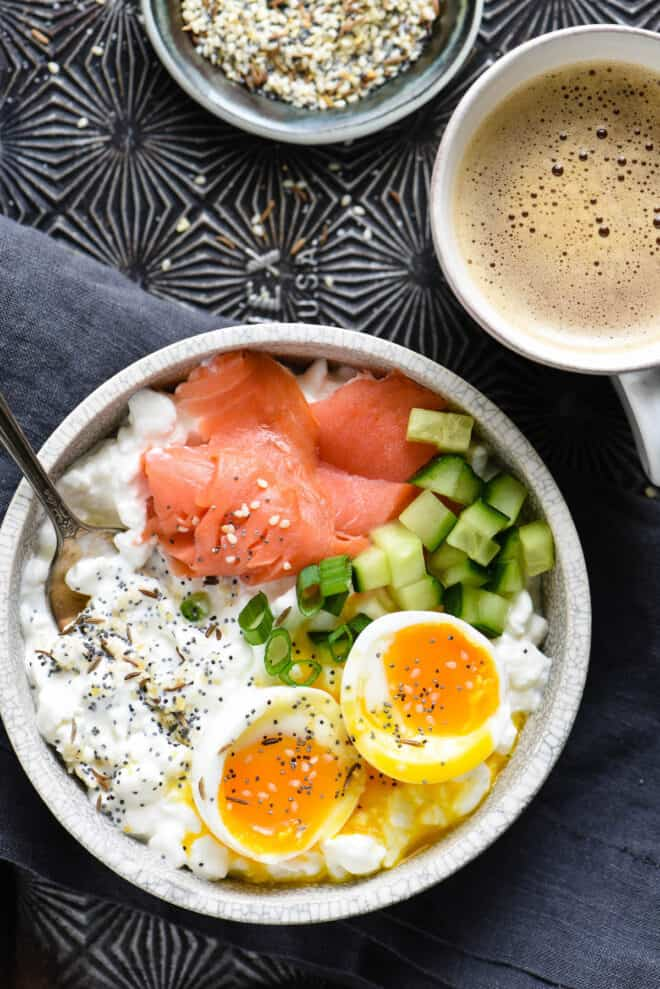 Savory cottage cheese bowl topped with lox, onions, cucumbers and soft egg, alongside mug of coffee and small bowl of seasoning mix.