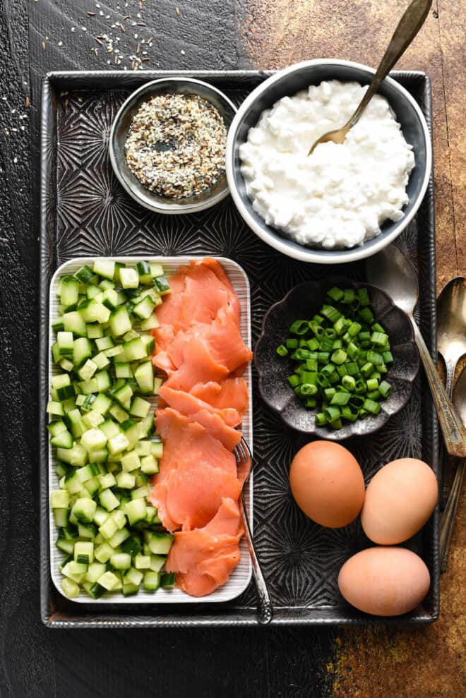 Baking pan with small dishes of everything bagel seasoning, cottage cheese, sliced green onions, brown eggs, chopped cucumber and smoked salmon.
