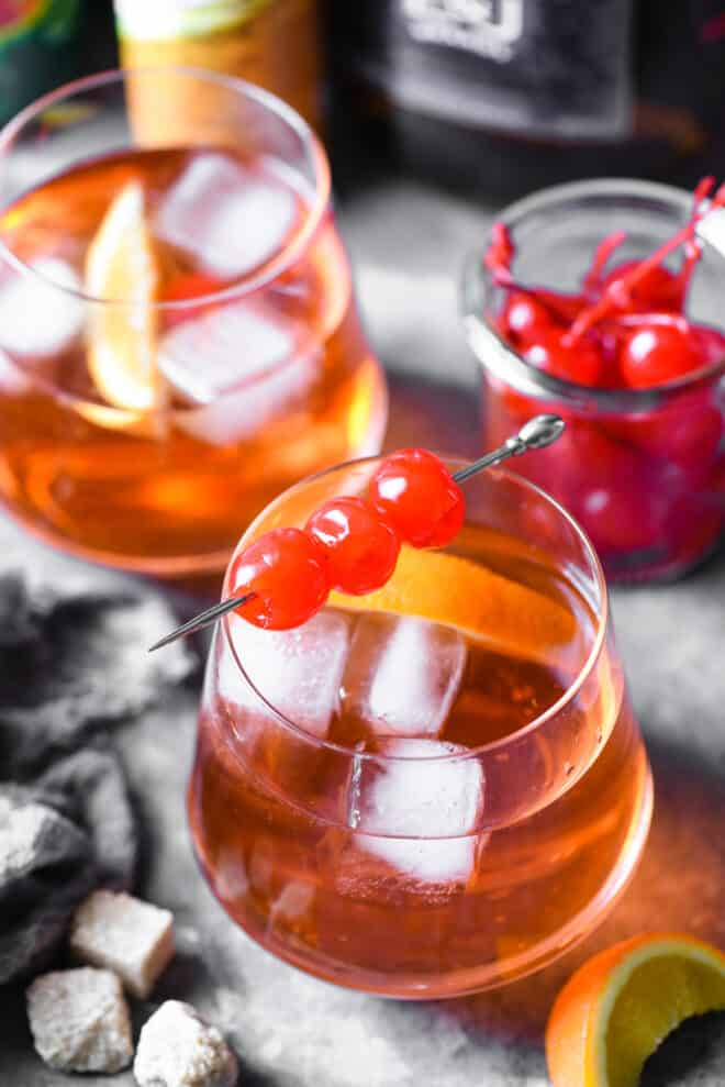 Two brandy old fashioneds garnished with maraschiono cherries and orange slices.