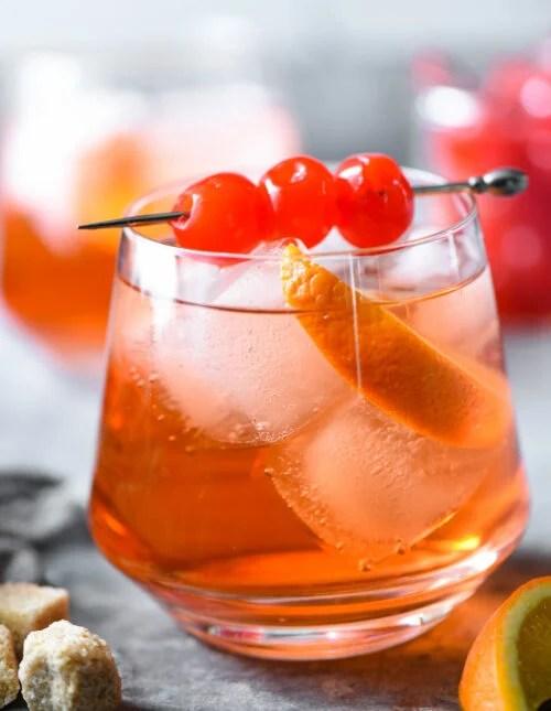 Orange hued cocktail with ice, orange slice and cherry skewer.