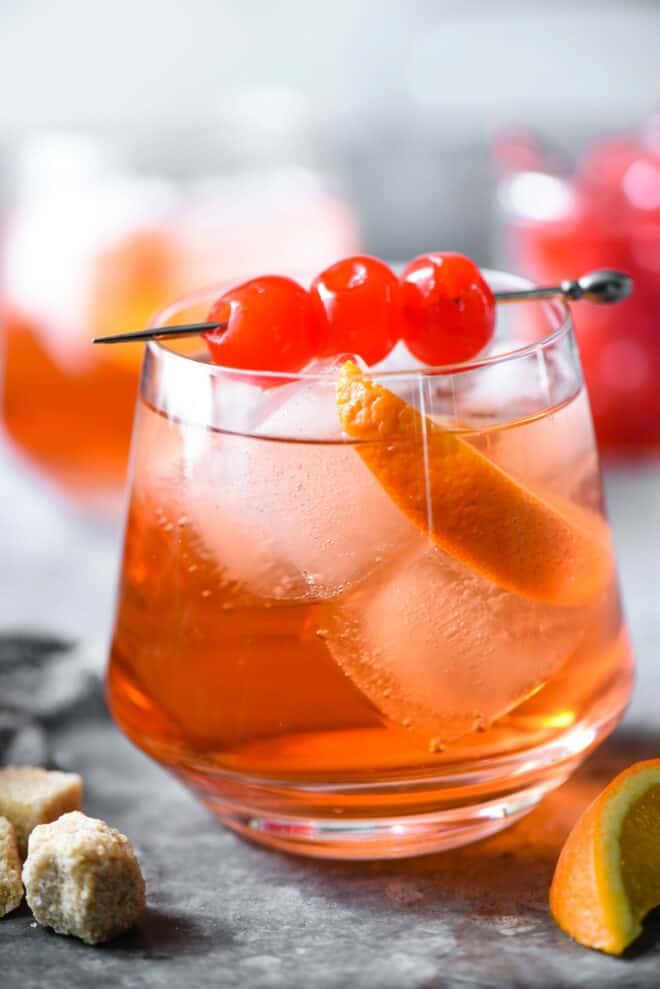 Orange hued cocktail with ice, orange slice and cherry skewer.