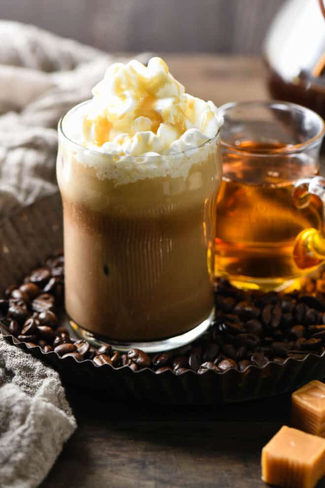 Small glass of coffee topped with whipped cream and caramel sauce.