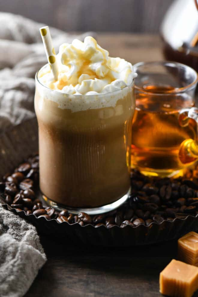 Small glass of coffee topped with whipped cream, caramel sauce and a polka dot straw.