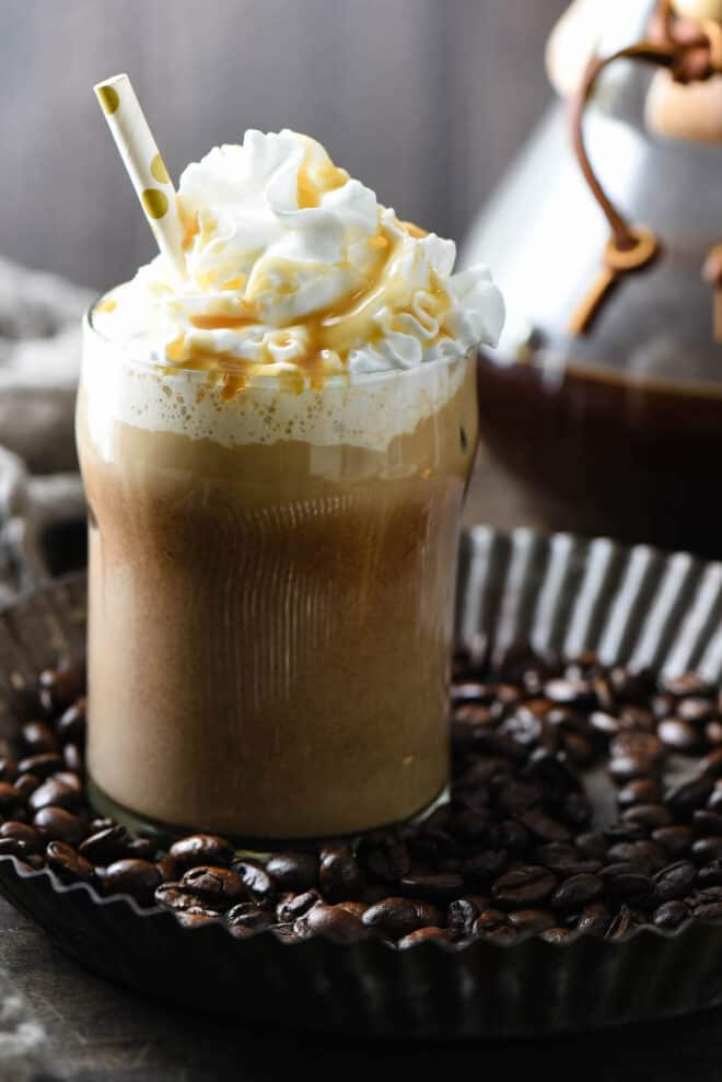 Small glass of espresso based drink topped with whipped cream, caramel sauce and a polka dot straw.