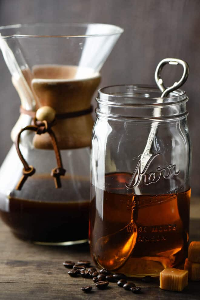Quart sized mason jar half filled with brown syrup, with spoon in it. Chemex coffee maker is in background, caramel candies and coffee beans are in foreground.