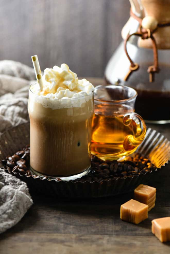 Small glass of iced coffee drink topped with whipped cream and caramel sauce, with a straw.