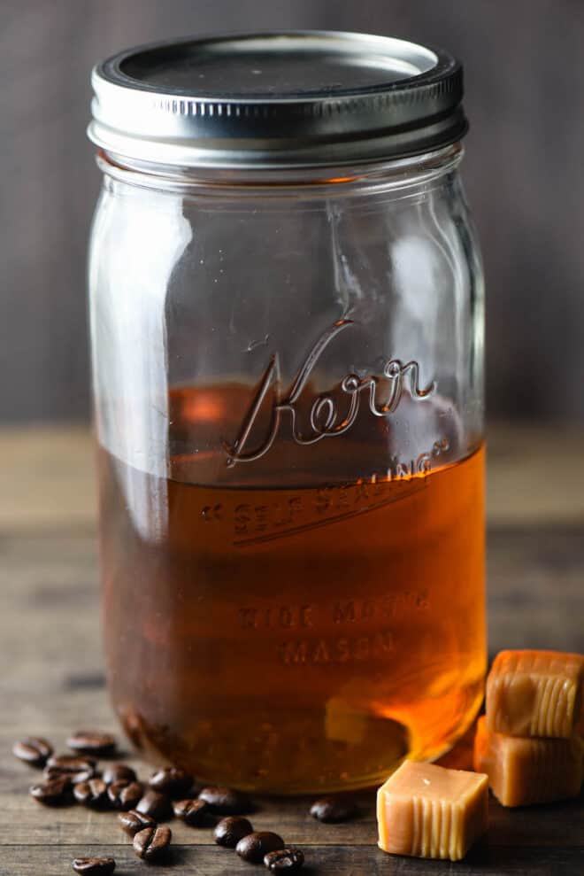 Quart sized mason jar half filled with brown syrup. Caramel candies and coffee beans are in foreground.