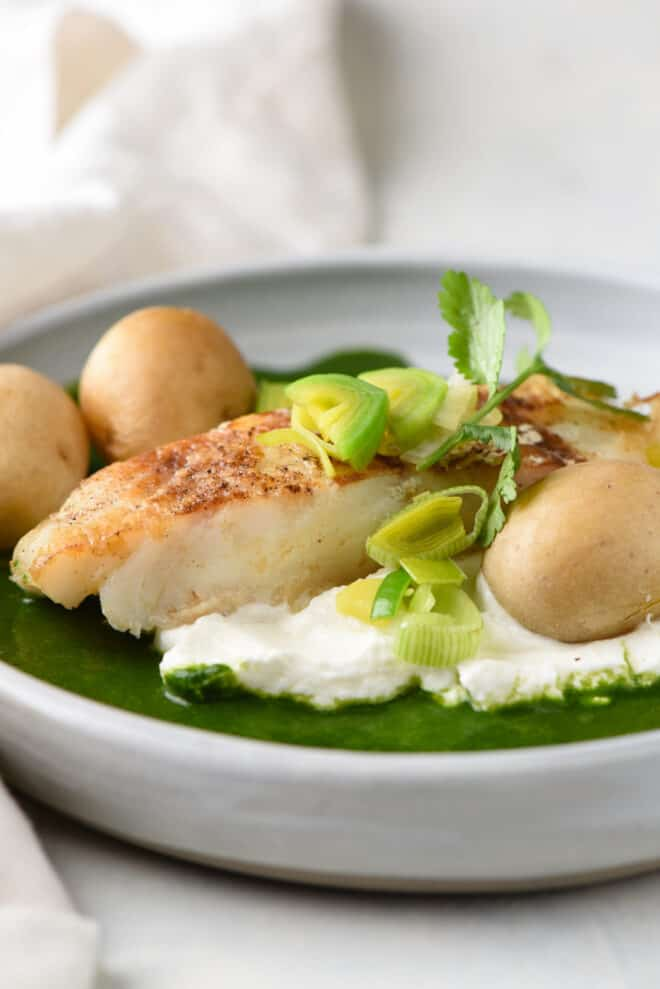 Pan seared Chilean sea bass, topped with leeks and cilantro, with yogurt, green sauce and potatoes.