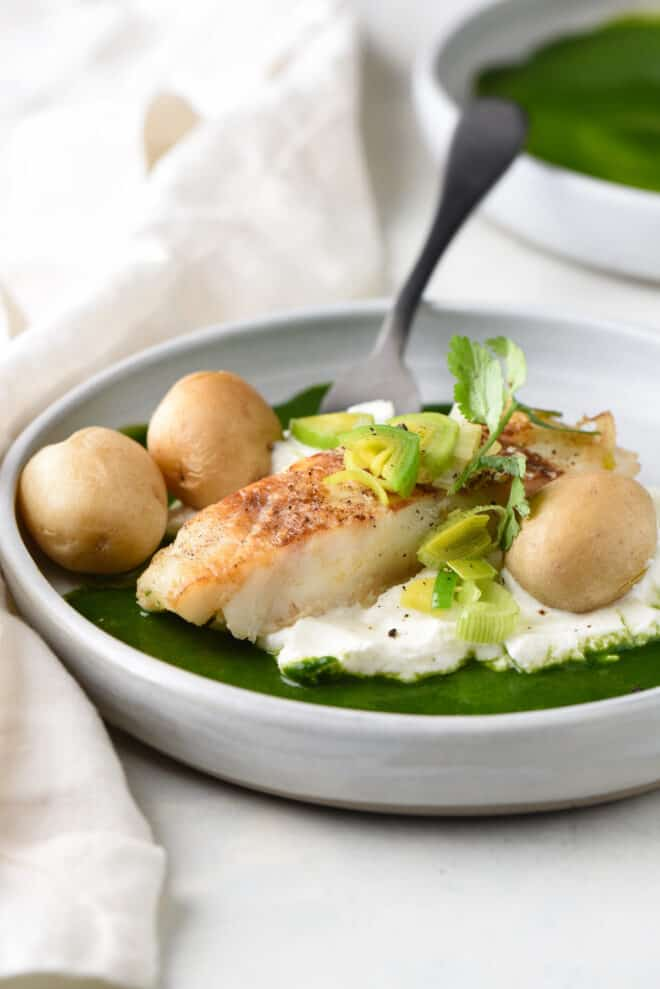 Shallow gray bowl filled with seared chilean sea bass, yogurt, a green sauce, and small boiled potatoes.