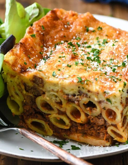 Large slice of Greek lasagna on white plate with green salad.