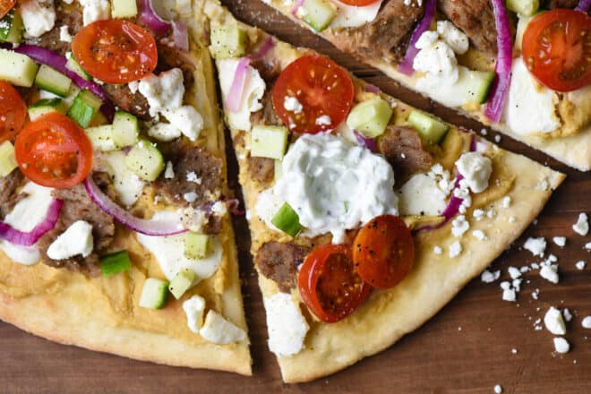 Closeup on flatbread topped with lamb meat, tomatoes, red onion, cucumber and tzatziki sauce.