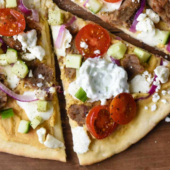 Closeup on slice of pizza topped with gyro meat, vegetables, and tzatziki sauce.