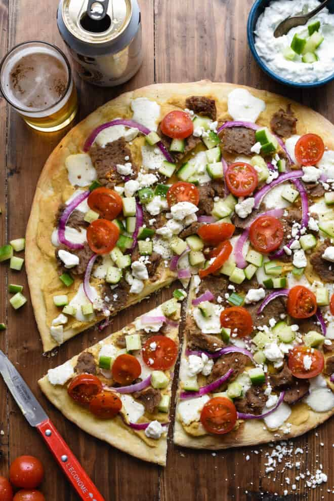Large gyro pizza with one slice cut out on wooden tabletop.